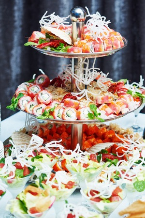 table setting: catering services background with asian snacks and sushi rolls on guests table in restaurant at event party