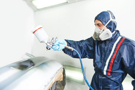 pulverizer: worker painting auto car bumper using spray gun in a paint chamber during repair work. Focus on pulverizer