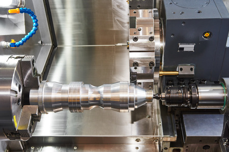 metalworking  industry: cutting steel metal shaft processing on lathe machine in workshop. Selective focus on tool Archivio Fotografico