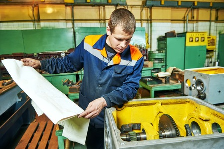 fettler: Adult experienced industrial worker assembling the reduction gear box on production line manufacturing workshop