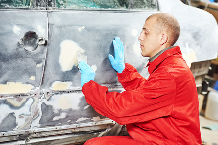 service station: auto mechanic worker applying car body filler at automobile repair and renew service station