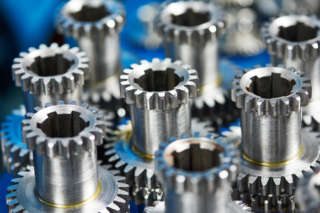 manufacturing equipment: close-up set of metal cog wheels gears details with splines Stock Photo