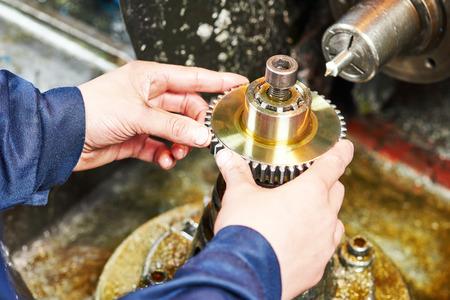 fémfeldolgozó iparban. Operator kezek telepítése fogú fogaskerék fogaskerék megmunkálási vágással malom eszköz.