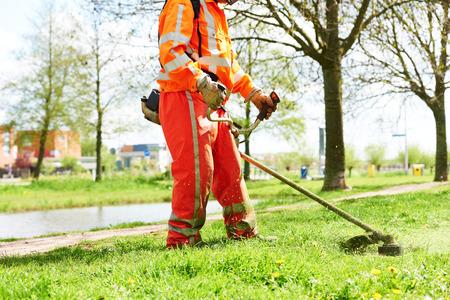 mantenimiento: cortadora de c�sped hombre trabajador de corte de hierba en el campo verde Foto de archivo