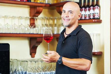 bocal: Portrait of sommelier barman holding a glass of water with wine glasses in the bar background