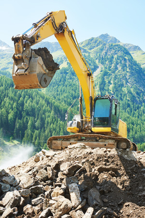 mining equipment: excavator loader machine during earthmoving works outdoors at mountain construction site