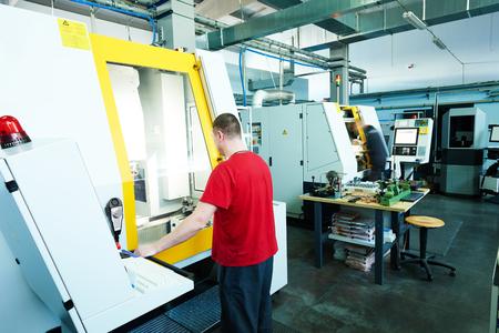 mechanische Industriearbeiter an CNC-Fräsmaschine Zentrum in Werkzeugbau Werkstatt. Authentisches Schießen unter schwierigen Bedingungen.