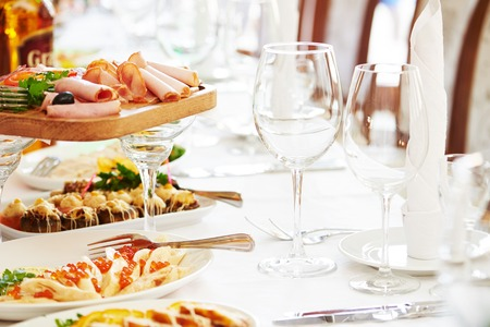 food industry: catering table set service with silverware, napkin and glass stemware at restaurant before party