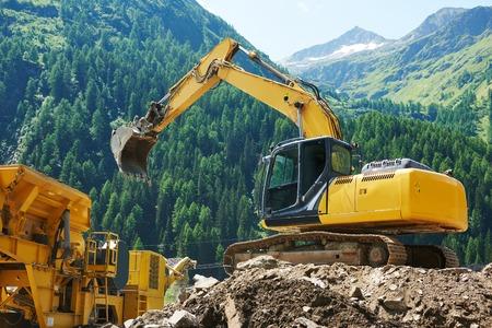 excavator loader machine loading dumper truck at construction site