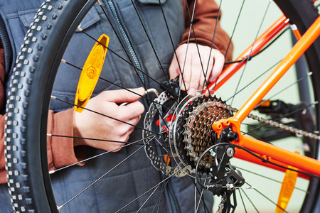 bicycle gear: Bike service: mechanic serviceman repairman installing assembling or adjusting bicycle gear on wheel in workshop