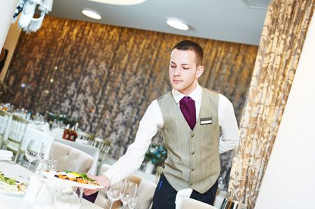 serving: Restaurant catering services. Male waiter with food dish serving banquet table Stock Photo