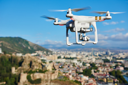 fly: drone quadrocopter with high resolution digital camera flying in the blue sky over the city Stock Photo