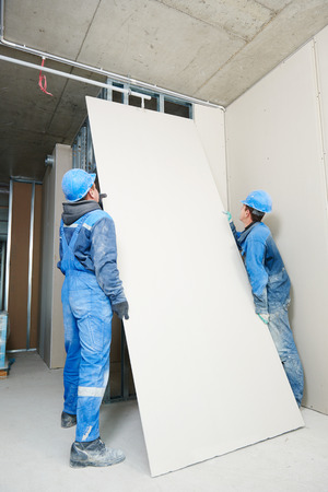 walling: gypsum plasterboard installation during indoor walling by workers Stock Photo