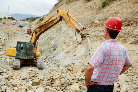 taskmaster: Earthmoving works. engineer builder watching construction machinery with hydrohammer
