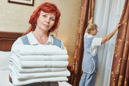 staff: Hotel service. Female housekeeping staff worker with towels in front of maid making bed in room