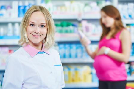 pharmaceutics: pregnancy and pharmaceutics theme. Smiling female pharmaceutist worker portrait with pregnant woman choosing medicine on background at pharmacy store Stock Photo