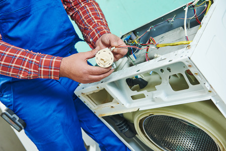 repairer: Washing machine repair. Repairer hands replasing with water level sensor pressure switch in front of damaged unit