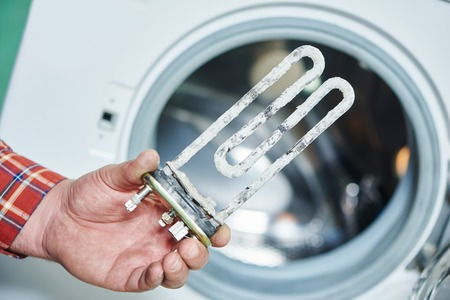 Washing machine repair. Hand of repairer with turbular electric heating element Stock Photo
