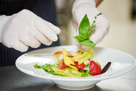 prepared dish: male cook chef decorating garnishing prepared salad dish on the plate in restaurant commercial kitchen Stock Photo