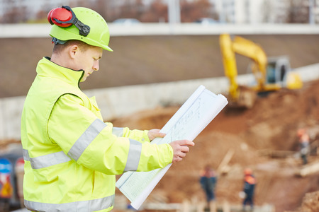 taskmaster: engineer builder with blueprint plan at construction site