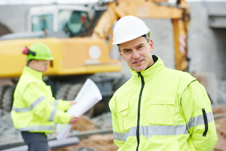 taskmaster: Portrait of engineer builder with colleague with blueprint plan at construction site with machinery