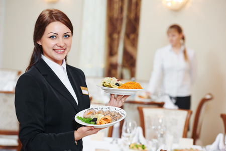 Restaurant catering services. Waitress with food dish serving banquet table Stock Photo - 49593495