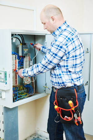 fuse box: electrician measure high voltage with electrical tester meter in fuse box