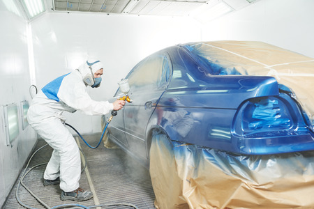 paint box: automobile repairman painter in protective workwear and respirator painting car body bumper in paint chamber Stock Photo
