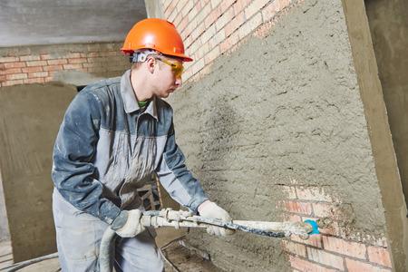 plasterer: Plasterer operating sprayer equipment machine for spraying thin-layer putty plaster finishing on brick wall