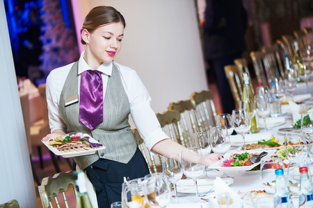 banquet table: Restaurant catering services. Waitress with food dish serving banquet table