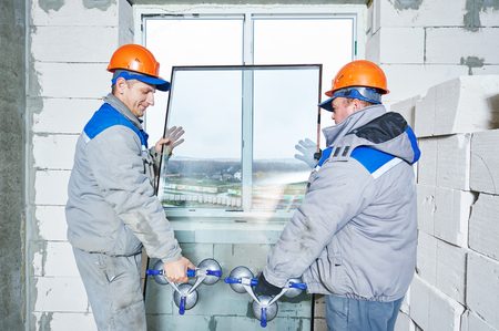 install: male industrial builders worker at window installation in building construction site Stock Photo