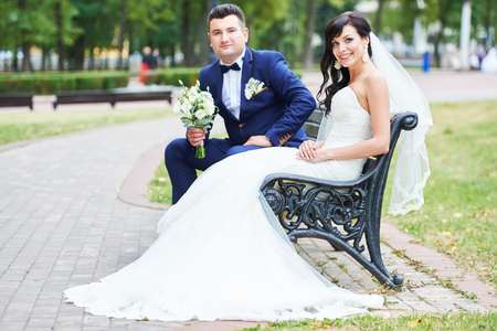 man sit: Wedding couple. Portrait of happy cheerful bride and  bridegroom with fresh flower bouquet sitting on bench outdoors in a park.
