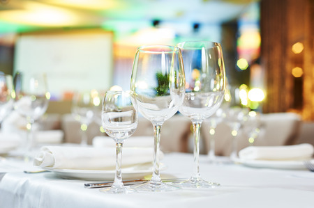 banquet table: Catering services. glasses set and dishes plates in restaurant before event