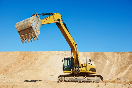 excavator machine at excavation earthmoving work in sand quarry Stock Photo
