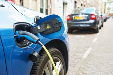 eco car: alternative eco energy fuel. Close up of the power supply plugged into an electric car being charged in Amsterdam Stock Photo