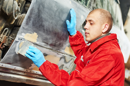 putty: auto mechanic worker applying car body filler at automobile repair and renew service station