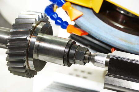 metalworking  industry. polishing and finishing metal cogwheel gear on grinding machine in factory