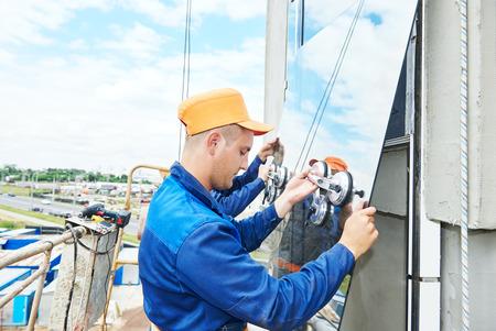 albañil: Dos constructores trabajador de la instalación de ventanas de vidrio en la fachada del edificio de negocios