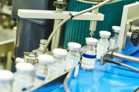 filling line: pharmaceutical industry. Close-up of glass bottles ampoules on the line machine conveyor at factory