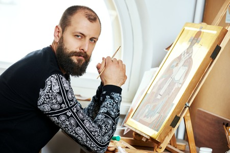 iconography: Iconography.  Portrait of religious icon painter man sitting in front of an orthodox icon with brush at workshop