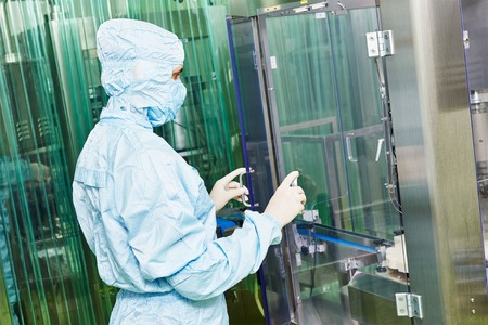 sterility: pharmaceutical factory woman worker in front of production line at pharmacy industry manufacture factory