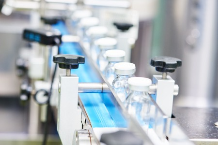 medicina: industria farmacéutica. Línea de producción transportador de la máquina con las botellas de vidrio ampollas en la fábrica, DOF bajo Foto de archivo