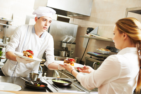 waitress: young male cook chef in white uniform gives to waitress plates with prepared meal in commercial kitchen Stock Photo