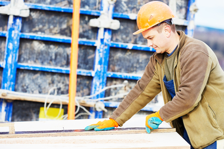 concreting: Concrete work. Male builder carpenter worker cutting plywood for falsework construction before concreting at building site