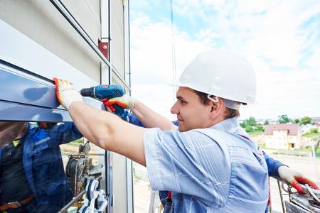 albañil: del constructor del trabajador con el taladro de mano de la instalación de ventanas de vidrio en la fachada del edificio de negocios