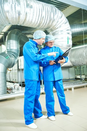 Two pharmaceutical technician male workers in water preparation production line hall at pharmacy industry manufacture factory using notebook computer