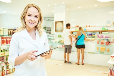 portrait of cheerful smiling female pharmacist working with tablet computer in pharmacy drugstore