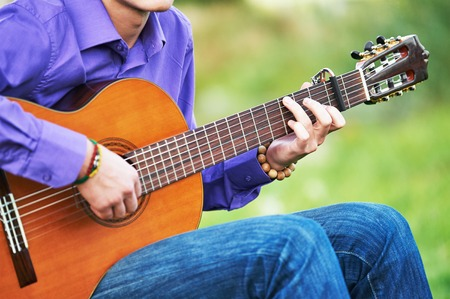 chords: Close up of guitarist hands playing music chords on acoustic six string guitar outdoors