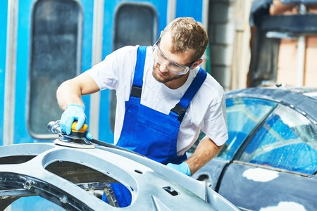 auto mechanic worker polishing bumper car at automobile repair and renew service station shop by power buffer machine Stock Photo