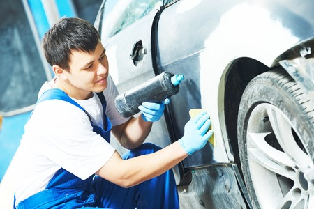 painting: auto mechanic worker applying washing car body preparing for painting at automobile repair and renew service station Stock Photo